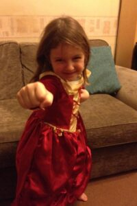 Girl in princess dress in martial arts pose.
