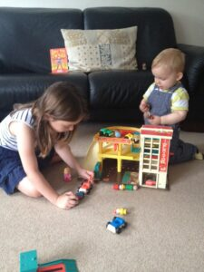 Girl and boy playing with Fisher Price garage and cars.