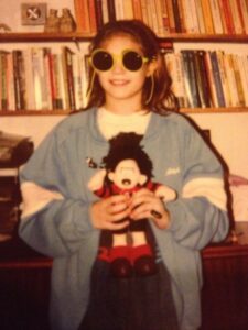 Girl in sunglasses with Dennis the Menace doll