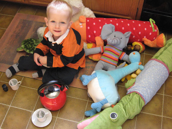 Young boy sitting on kitchen floor with cuddly toys, red kettle and teacups.