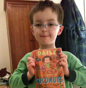 Boy holding 'Daisy and the trouble with coconuts'