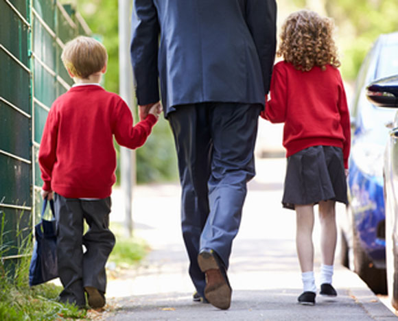 Two children in school uniform walking holding hands with a man.