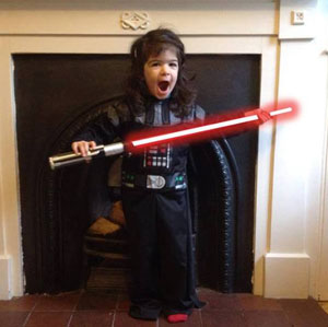 Young girl in Darth Vader costume with light sabre