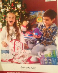 Boy and girl opening presents together next to a Christmas tree - boy has Hatchimal toy