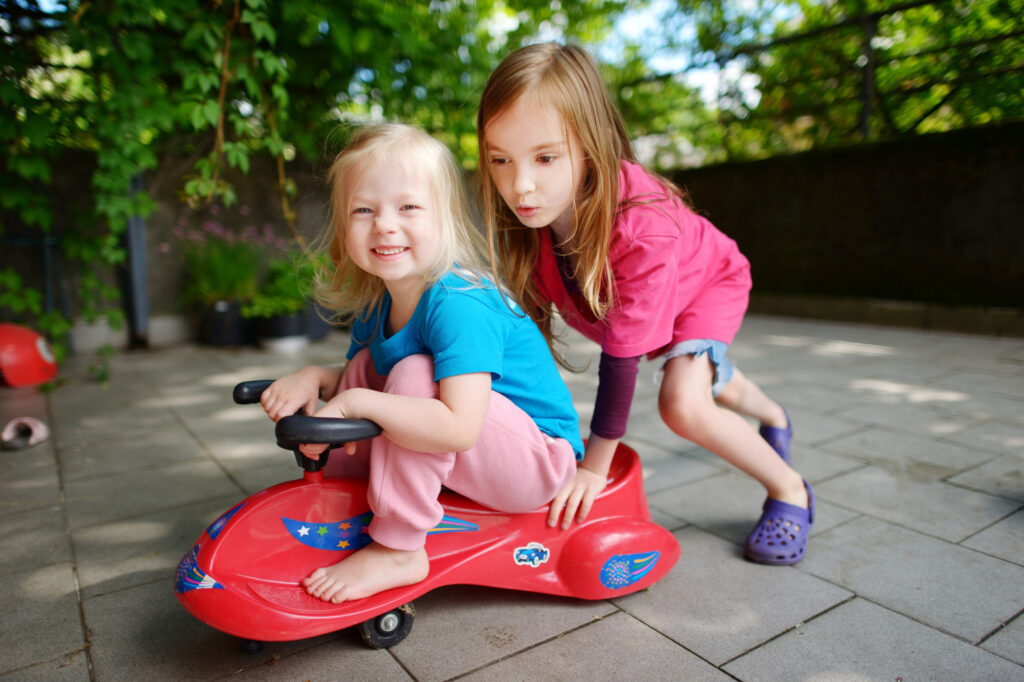 Two preschool age girls playing with a ride-on toy