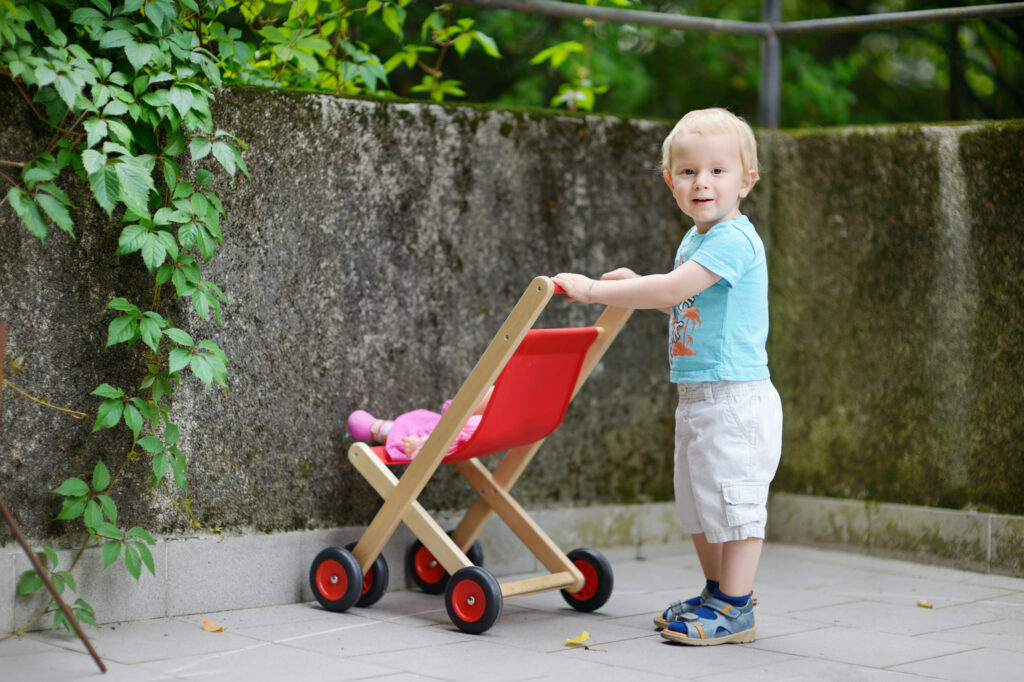 Boy with red toy pushchair and doll