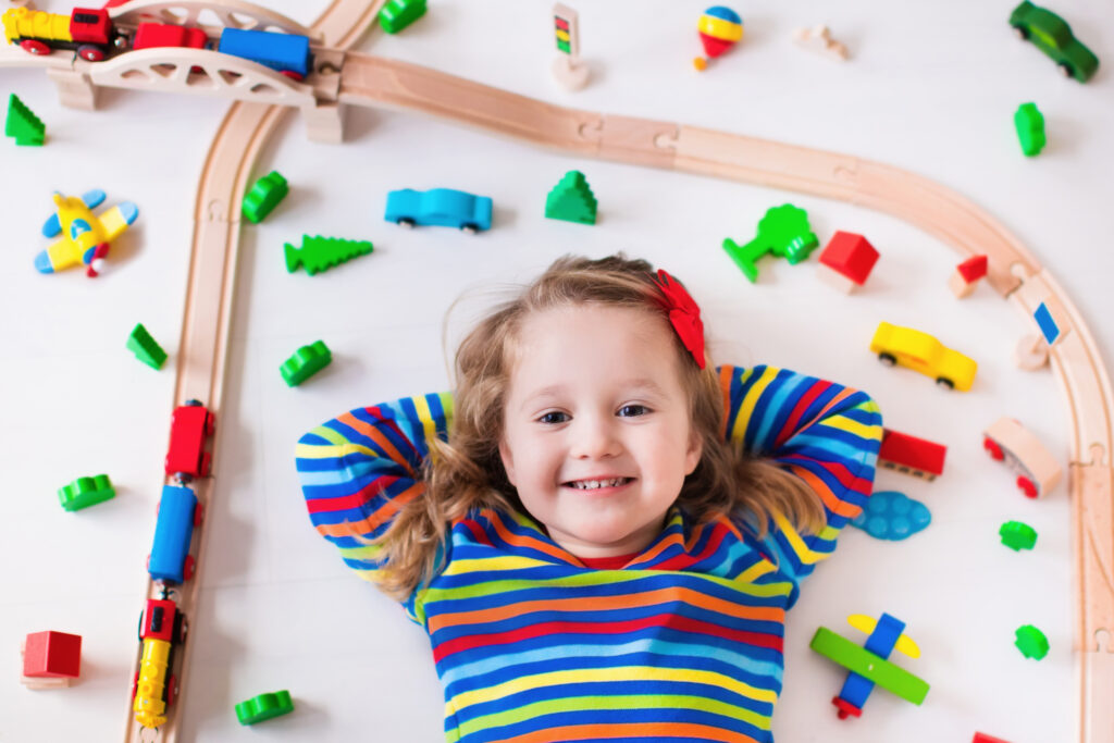 girl in stripy top surrounded by train track